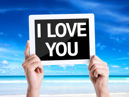 express feelings: Hands holding tablet pc with I Love You on beach background Stock Photo