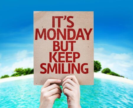 Hands holding cardboard with text It's Monday But Keep Smiling on beach background