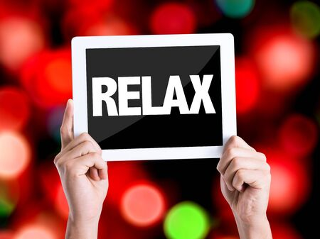 loosen up: Hands holding tablet with text Relax on bokeh background
