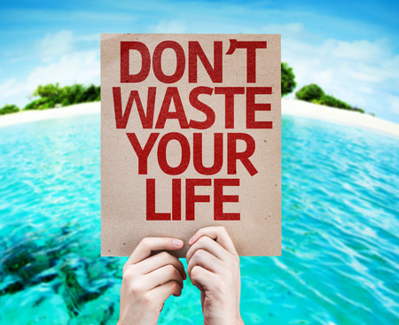 purposeful: Hands holding cardboard with Dont Waste Your Life on island background Stock Photo