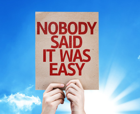 complicated journey: Hands holding cardboard with Nobody Said It Was Easy on sunny background