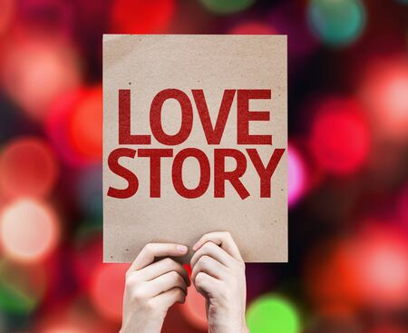 love story: Hands holding cardboard with Love Story on bokeh background Stock Photo