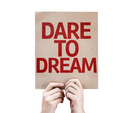 Hands holding cardboard with Dare to Dream on white background Stock Photo
