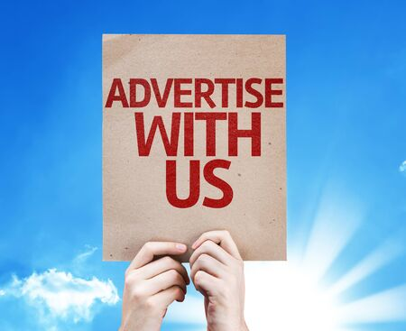 advertise with us: Hands holding cardboard with Advertise with Us on sunny background