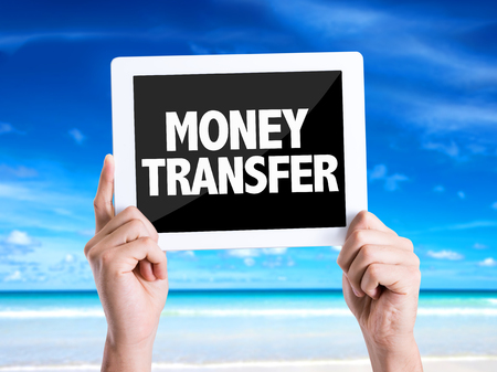 transfering: Hands holding tablet pc with Money Transfer on beach  background Stock Photo