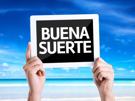 Manos que sostienen la PC de la tableta con buena suerte en español en el fondo de playa