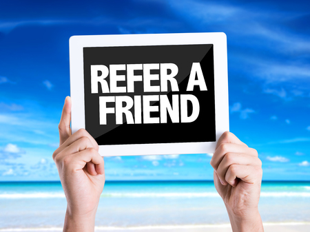 refer: Hands holding tablet pc with Refer A Friend on beach background