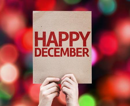 Hände halten Karton mit glücklichem Dezember auf Bokeh Hintergrund Standard-Bild