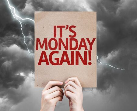 workday: Hands holding cardboard with Its Monday Again on stormy background