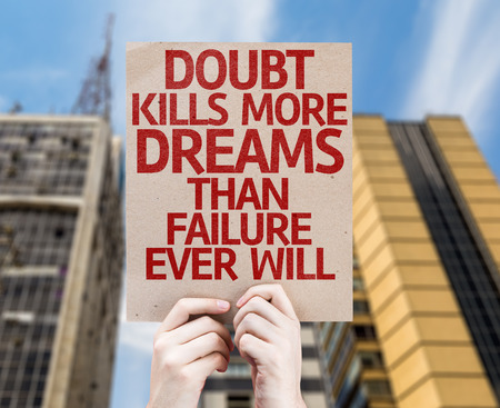 dreams of city: Hands holding cardboard with Doubt Kills More Dreams Than Failure Ever Will on city background Stock Photo