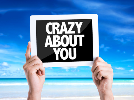 about you: Hands holding tablet pc with Crazy About You on beach background