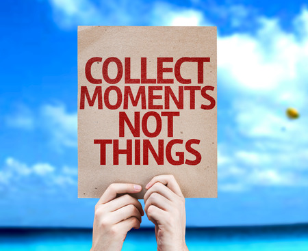 juntar: Hands holding cardboard with text Collect Moments Not Things on sea background