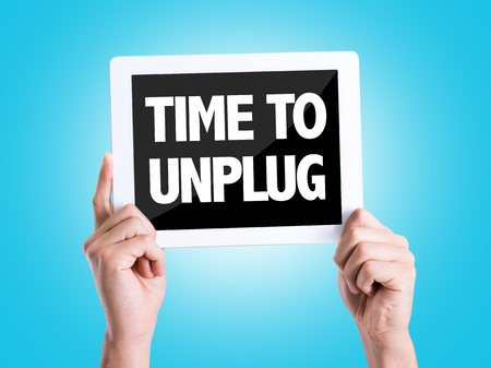 Hands holding tablet pc with Time To Unplug on blue background