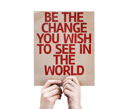 be the change: Hands holding cardboard with Be The Change You Wish To See In The World on white background