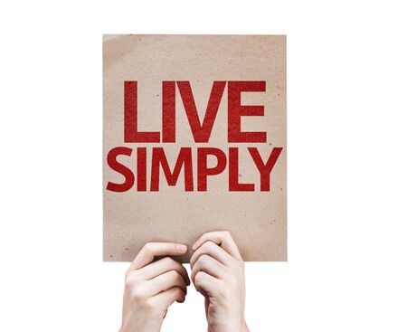 simply: Hands holding cardboard with Live Simply on white background Stock Photo