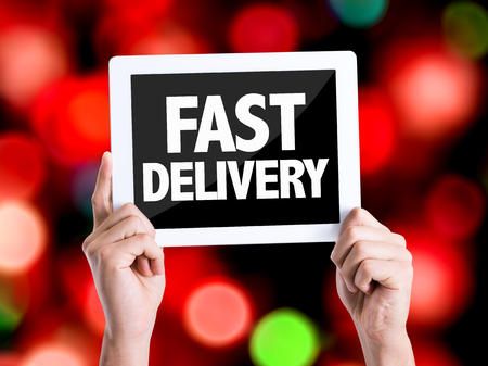 package sending: Hands holding tablet pc with Fast Delivery on bokeh background