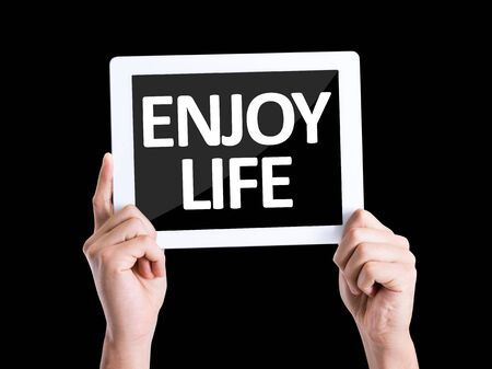 enjoy life: Hands holding tablet pc with Enjoy Life on black background