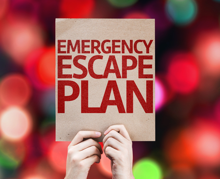 emergency plan: Hands holding cardboard with Emergency Escape Plan on bokeh background