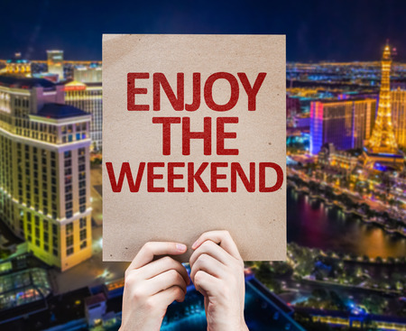 sayings: Hands holding cardboard with Enjoy The Weekend on city background