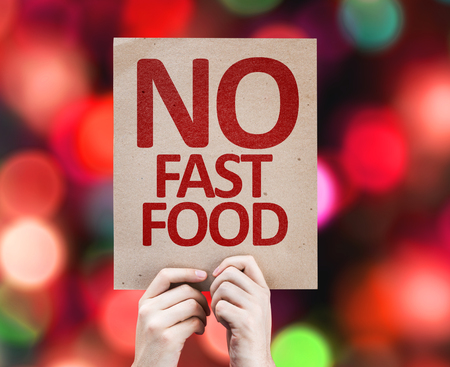 no food: Hands holding cardboard with No Fast Food on bokeh background