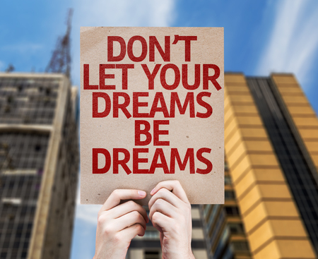 dreams of city: Hands holding cardboard with Dont Let Your Dreams Be Dreams on city background Stock Photo