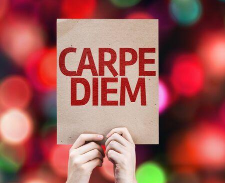 carpe diem: Hands holding cardboard with carpe diem on bokeh background Stock Photo