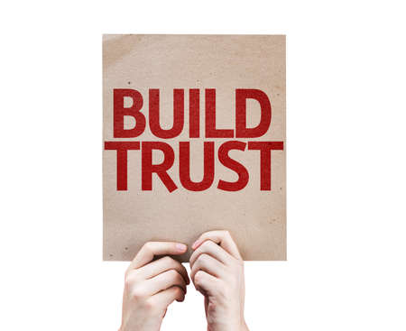 trusting: Hands holding cardboard with Build Trust on white background Stock Photo