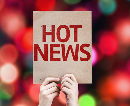 hot news: Hands holding cardboard with Hot News on bokeh background Stock Photo
