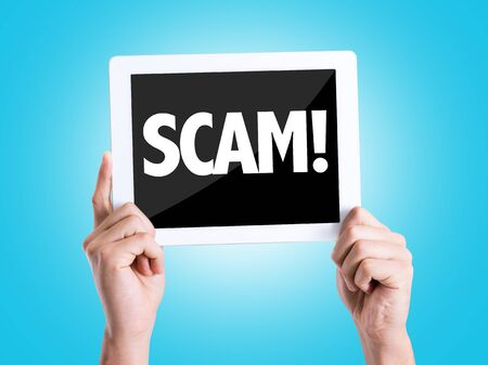 adware: Hands holding tablet pc with Scam on blue background