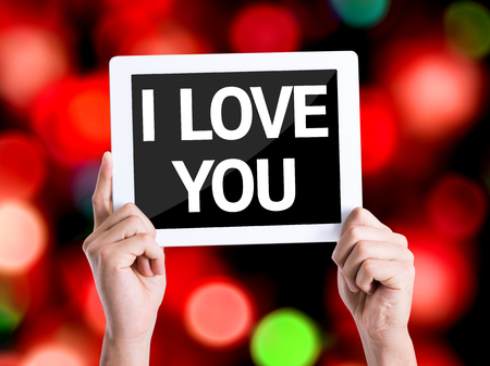 express feelings: Hands holding tablet pc with I Love You on bokeh background