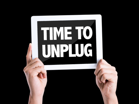 conservation: Hands holding tablet pc with Time To Unplug on black background Stock Photo