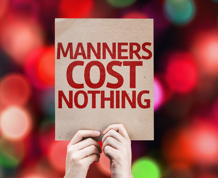 manners: Hands holding cardboard with Manners Cost Nothing on bokeh background