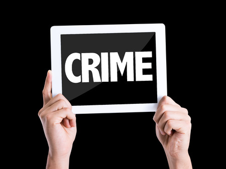 crime: Hands holding tablet pc with Crime on black background Stock Photo