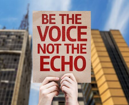 echo: Hands holding cardboard with Be The Voice Not The Echo on city background