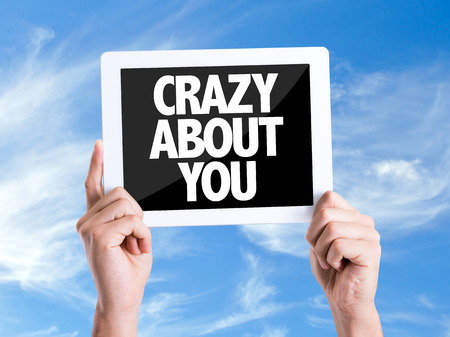 about you: Hands holding tablet pc with Crazy About You on sky background Stock Photo