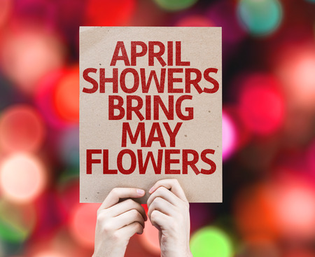showers: Hands holding cardboard with April Showers Bring May Flowers on bokeh background Stock Photo