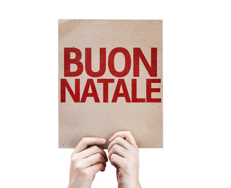 buon: Hands holding cardboard with Merry Christmas in Italian on white background