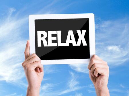loosen up: Hands holding tablet with text Relax on sky background