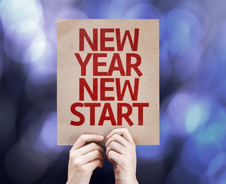 new start: Hands holding cardboard with New Year New Start on bokeh background