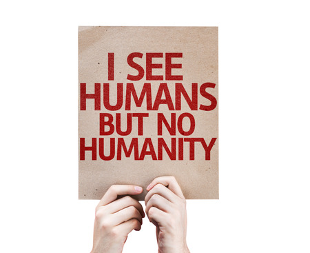 hostility: Hands holding cardboard with I See Humans But No Humanity on white background