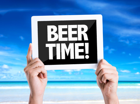 beer after work: Hands holding tablet pc with Beer Time on beach background