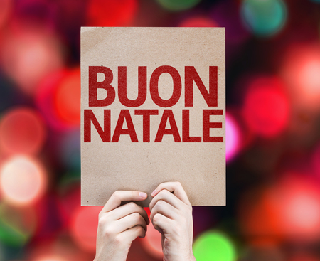 buon: Hands holding cardboard with Merry Christmas in Italian on bokeh background Stock Photo