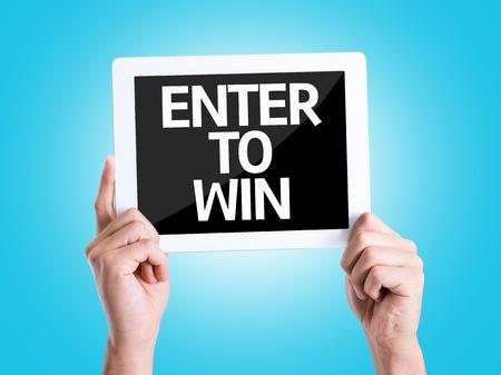 competition: Tomados de la mano de cartón con entrar para ganar en el fondo azul Foto de archivo