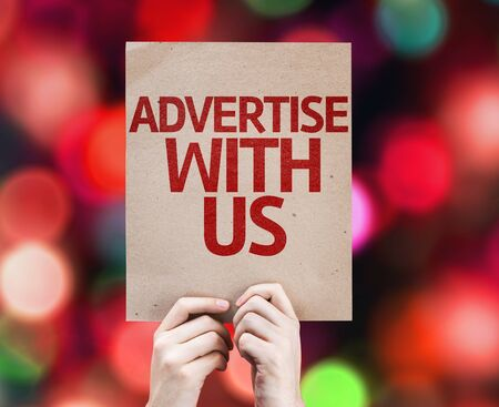 advertise: Hands holding cardboard with Advertise with Us on bokeh background