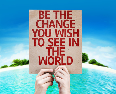 be the change: Hands holding cardboard with Be The Change You Wish To See In The World on island background
