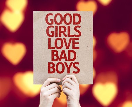 good bad: Hands holding cardboard with Good Girls Love Bad Boys on heart bokeh background