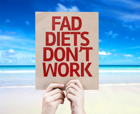 fad: Hands holding cardboard with Fad Diets Dont Work on beach background