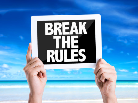 break the rules: Hands holding tablet pc with Break The Rules on beach background Stock Photo