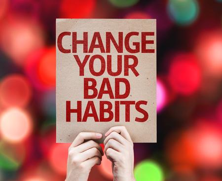 malos habitos: Tomados de la mano de cartón con cambiar sus malos hábitos en el fondo del bokeh