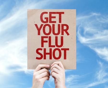 Handen die tablet pc met Get Your griepprik op de hemel achtergrond